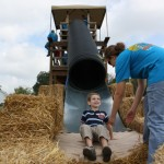 A child looks up at a Fall on the Farm staff worker after shooting down the slide.