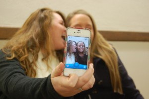 Lexi Sosh, junior from Evansville, Ind., and Taylor Strohmeier, junior from Louisville, Ky., take a Snapchat photo with a smartphone. || Anna Taylor/The News