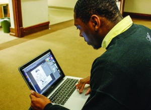 Kory Savage, junior from Clinton, Ky., sketches his shirt designs for his clothing line, Savy Brands Clothing, and then brings the designs to life on his laptop. || Kristen Allen/The News
