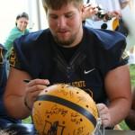 Senior Casey Duncan signs a helmet.