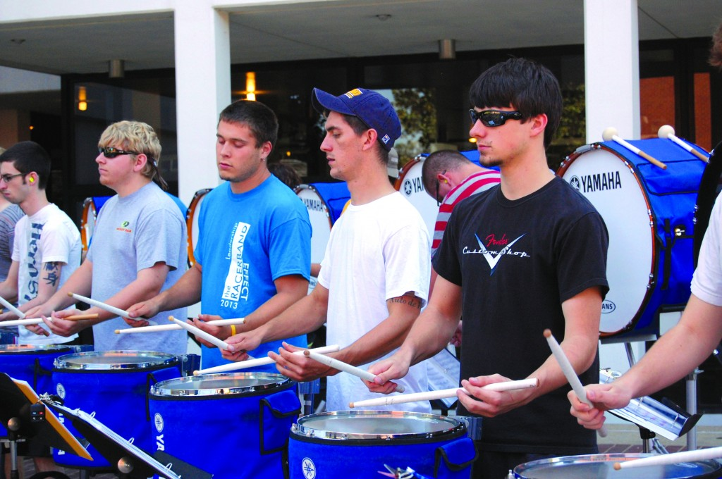 Emily Clark/The News Members of the Racer Band drumline entertain students passing by outside of Price Doyle Fine Arts Center.