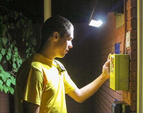 Kate Russell/The NewsAaron Burkeen, a sophomore from Murray, checks one of the many call boxes on campus.