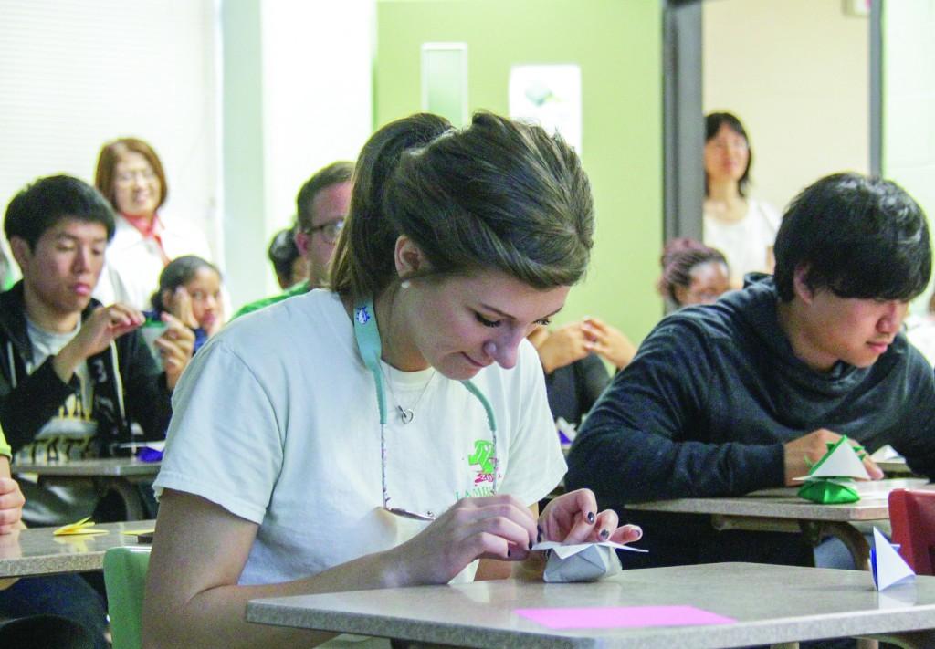 Lori Allen/The News Junior Britney Boston practices origami skills at origami night last week.