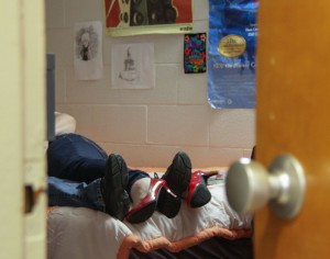 Photo illustration by Lori Allen//The News / Two students are shown in a bed in a residential college. Many students are upset by a new visitor policy, which prohibits students from having overnight visitors during the week.
