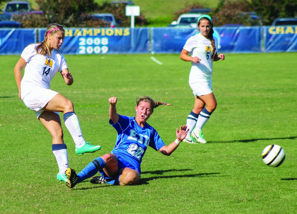 Jenny Rohl/Contributing Photographer Freshman Lauren Frazier passes the ball past a sliding Eastern Illinois defender during Sunday's match at Cutchin Field.