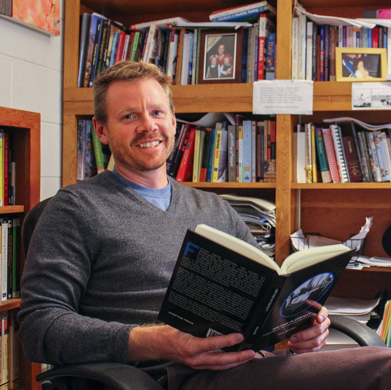 "Kate Russell/The News Paul Walker, associate professor of English, sits in his office with his recently published book, ""Writing in Context: Composition in First-Year Learning Communities."""