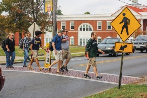 Kate Russell/The News Students cross 16th Street on one of the crosswalks with a safety sign in the middle of it. This sign was replaced after being hit by several vehicles.