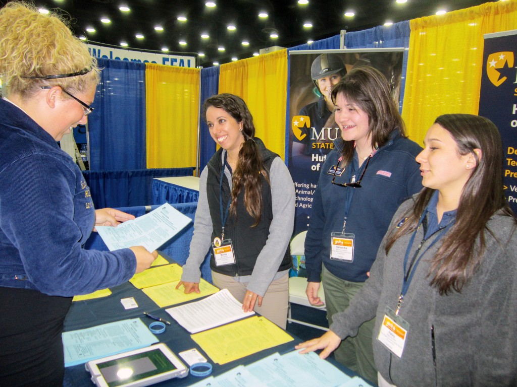 Alex Mahrenholz/The News Murray State FFA seniors Marisa Bedron and Samantha Anderson, and sophomore Hayley Barfield, talk to high school FFA members at the 86th National FFA convention last week.