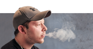 Photo illustration by Ana Bundy and Lori Allen/The News Toby Monts, freshman from Murray, puffs on an e-cigarette indoors. Monts only smokes e-cigarettes occasionally because he said they do not have the same effect as a regular cigarette.