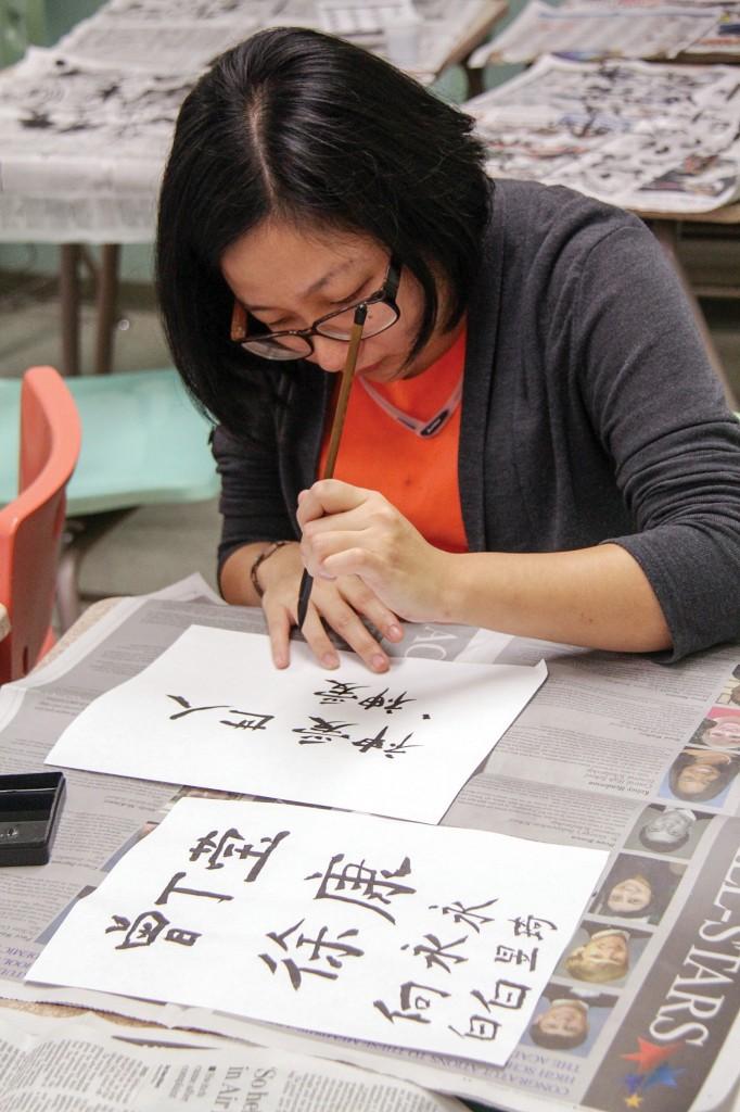 Lori Allen/The News Esther Chen, international graduate student from Malaysia, practices writing the Bible verse John 3:16 in Chinese characters at a calligraphy workshop held during International Education Week