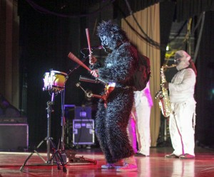 "Lori Allen // The News /// Java entertains on stage in a gorilla costume with a strapped on bell instrument which he plays at the same time as a set of drums during the song ""Petting Zoo Gorilla."""