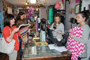 Torrey Perkins/The News Ribbon Chix employees ringup a customer's purchases after she finishes shopping.