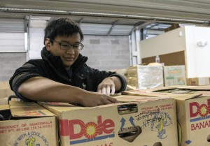 Kate Russell/The News Blake Lin, a sophomore from China, helps load boxes at Need Line for the move to its new building.