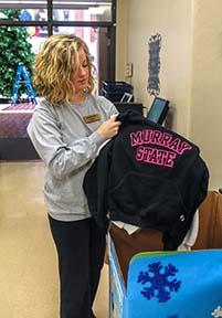Jenny Rohl / The News University Store employee Tessa Springer sorts donated sweatshirts.