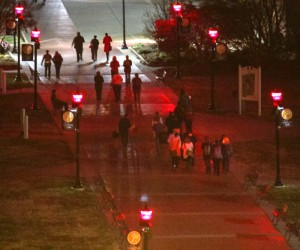 Lori Allen // The News ///  Walkers are lit not only by the candles they carry, but by the lights down the main strip of campus, turned red for the Red Week events, raising HIV/AIDS awareness.