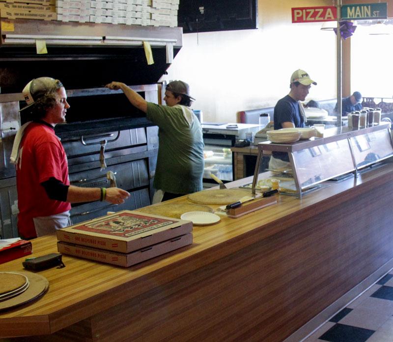Lori Allen/The News Matt B's workers prepare pizza in their newly renovated restaurant on Main Street.