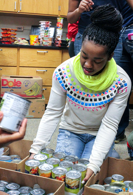 Jenny Rohl/The News Western Kentucky University student Ashney Williams helps Murray State students and members of Delta Sigma Theta pack the new food pantry called Racers Helping Racers.