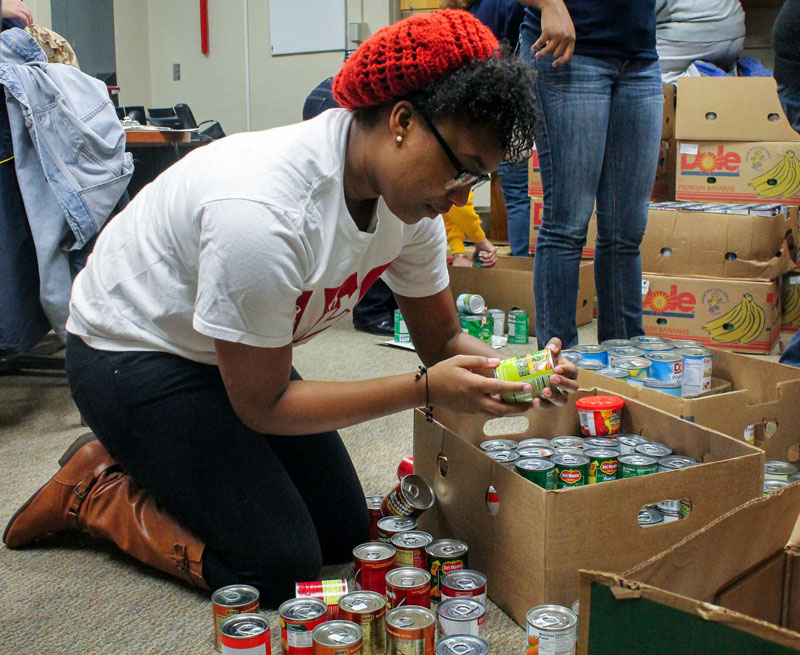 Jenny Rohl/The News Delta Sigma Theta member, Jovon Richmond, graduate student from Louisville, Ky., helps unload canned goods Monday during the Martin Luther King Jr. Day of Service.