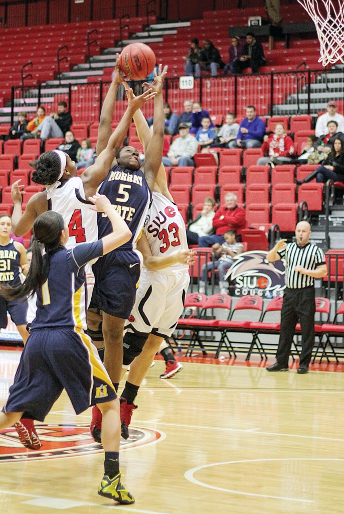 Photo by Lori Allen, illustration by Evan Watson/The News Senior forward Jessica Winfrey attempts a shot in the Racers' loss Saturday.