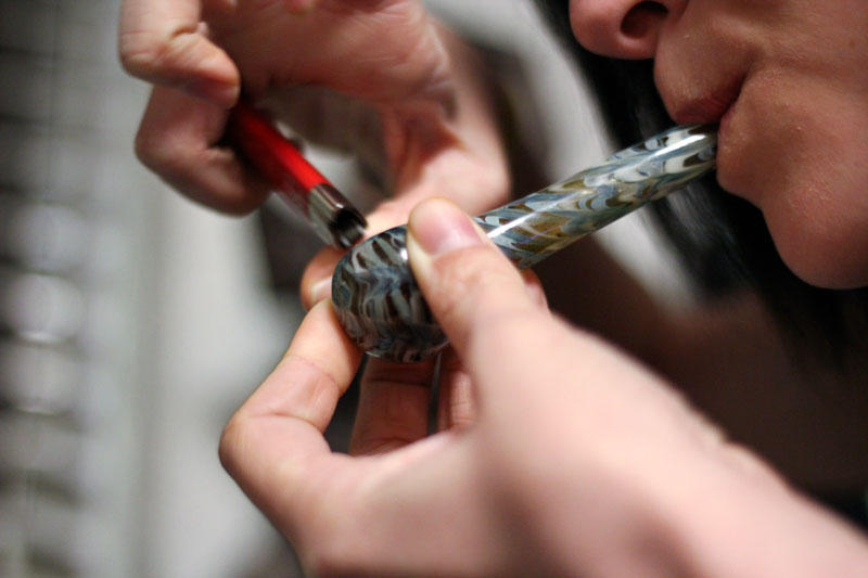 Kate Russell/The News A?student lights a glass pipe, used to smoke marijuana, in one of the residential colleges on campus.