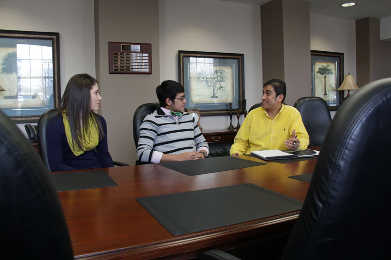 Lori Allen/The News Madison Embry, junior from Morgantown, Ky., and Topaz Prawito, sophomore from Murray, discuss with the new director of Volunteer Income Tax Assistance program, Ray Rodriguez.