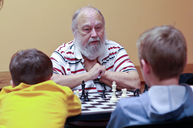 "Fumi Nakamura/The News Wayne Bell, chess club adviser, teaches Murray youth a strategy game related to chess called ""The Peasant's Revolt."""