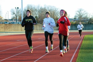 Jenny Rohl/The News Juniors Brittany Bohn (left) and Abbie Oliver (right) run around the track in a morning practice.