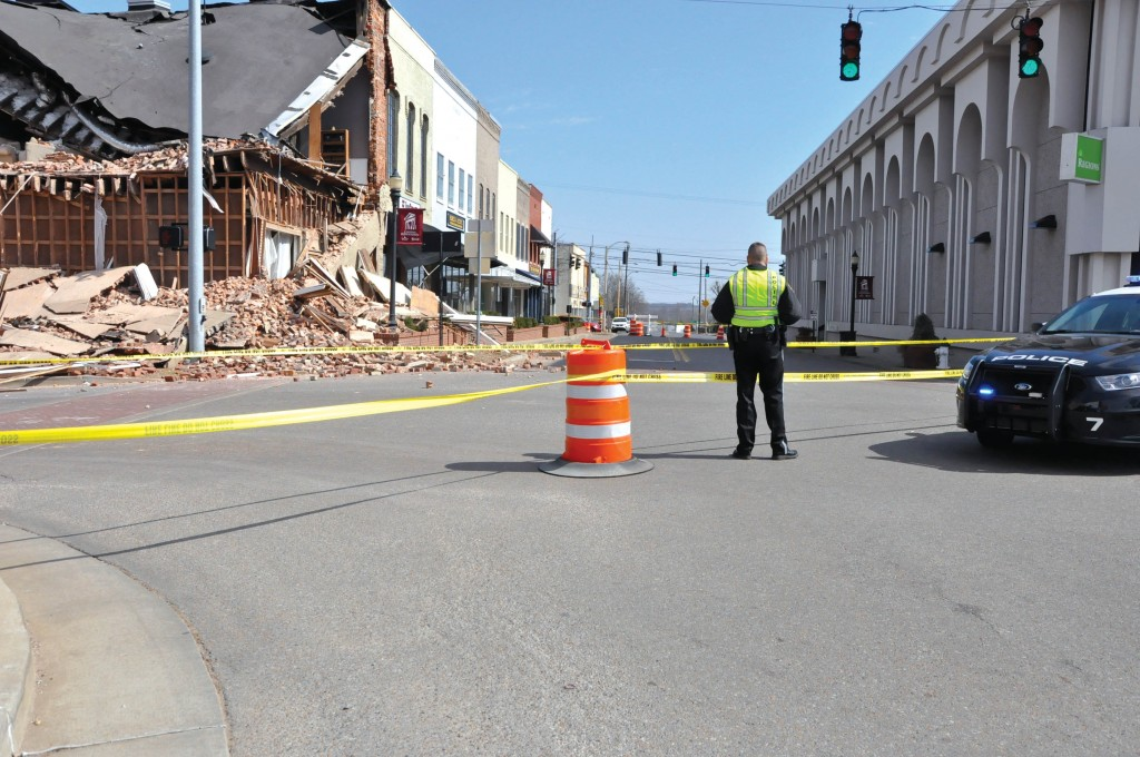 Ana Bundy/The News A police officer stands near the site of Saturday's building collapse.