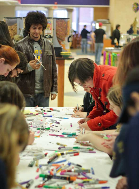 Lori Allen/The News A line of students celebrates Mardi Gras in Winslow Dining Hall by making colorful, festive masks.