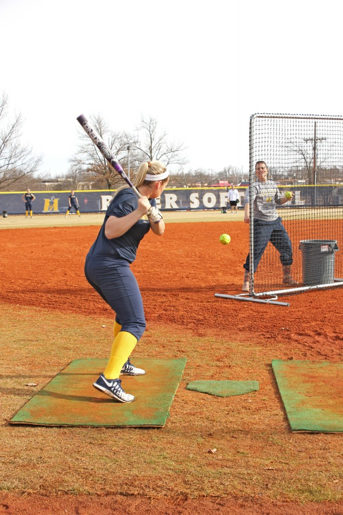 Kate Russell/The News Freshman Taylor Odom takes batting practice from Head Coach Kara Amundson.