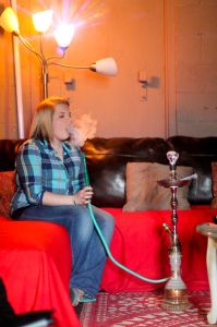 Jenny Rohl/The News Elisha Cherry, employee of The Breakaway Lounge, smokes hookah.