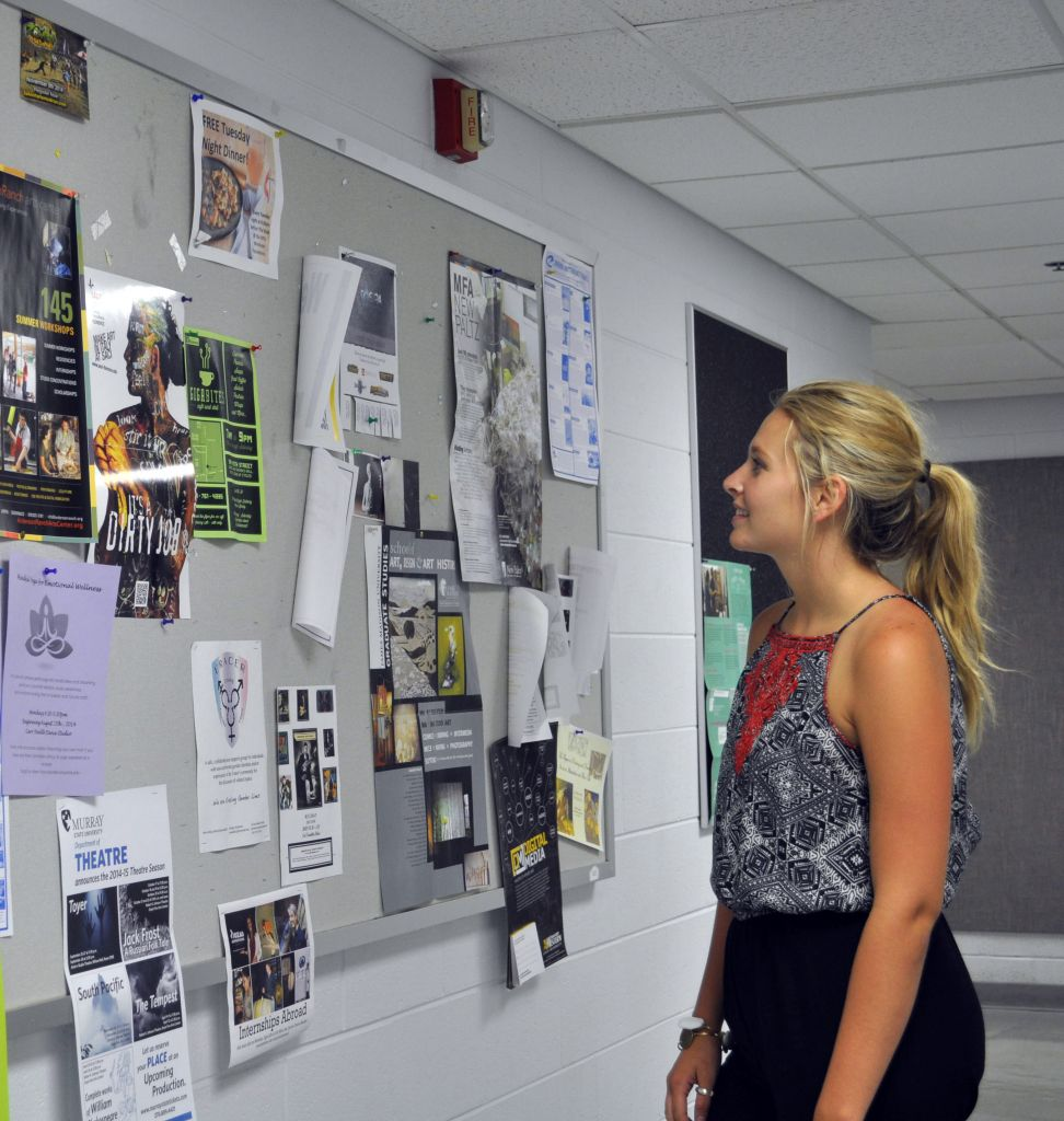 Kylie Townsend/The News Art major Abby Murdock, junior from Murray, looks at the upcoming events offered by the theater department.