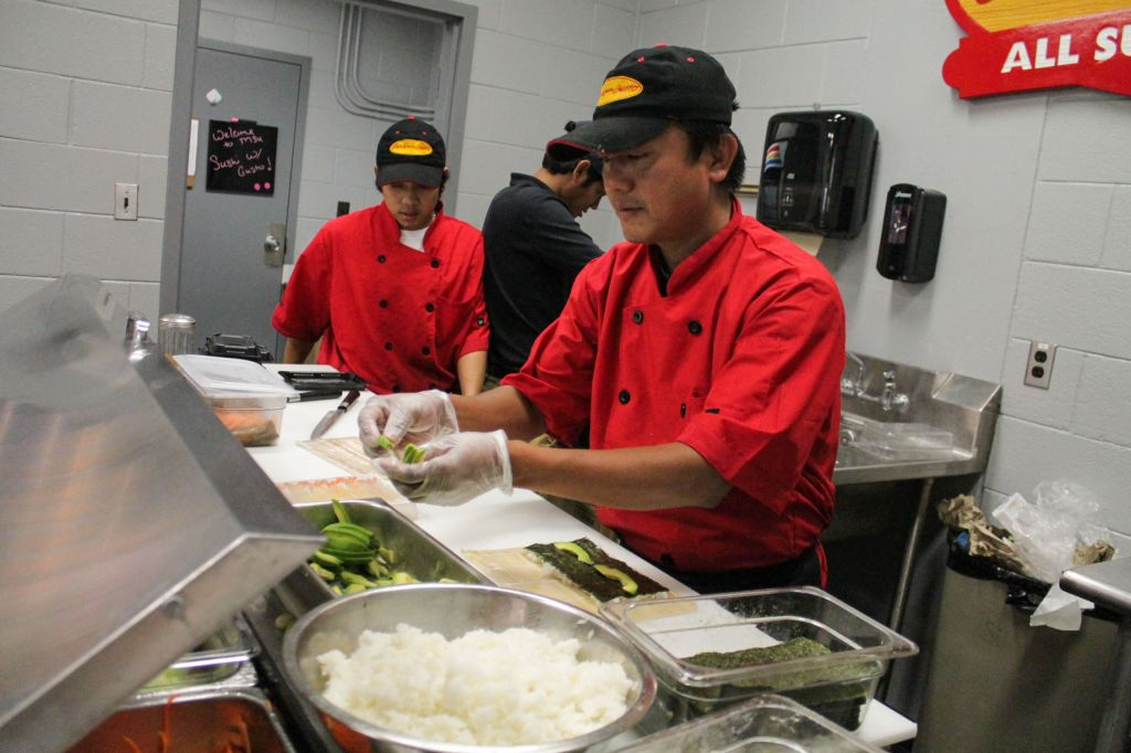 Jenny Rohl /The News Sushi chef Maung Tueng prepares sushi roll ingredients for the University's newest place to eat, Market '22, located in the Curris Center.
