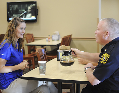 Kylie Townsend/The News Amber Miller, graduate student from Owensboro, Ky., talks with a police officer over a cup of coffee in the Thoroughbred Room Wednesday.