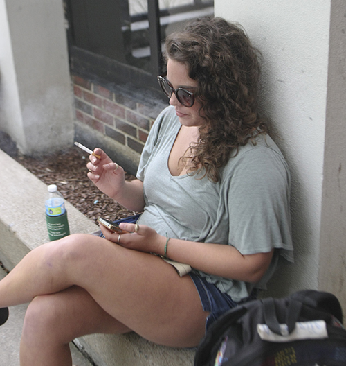 Haley Hays/The News A student sits outside of Faculty Hall between classes. Students, faculty and staff can't smoke on the side of the building that faces 16th Street.