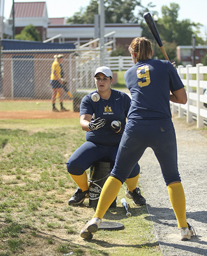 Haley Hays/The News Freshman pitcher Haven Campbell tosses balls to senior outfielder Mallory Richardson at practice Wednesday at Racer Field.