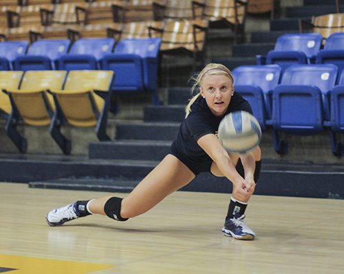 Jenny Rohl/The News Junior Emily Schmahl digs for a ball during practice in Racer Arena. The Racers are undefeated in tournament play and are looking forward to the start of regular season.