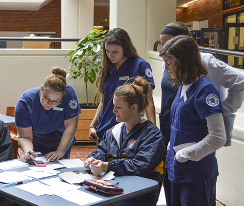 Hannah Fowl/The News Health Services employees and nursing students tally the number of vaccines administered at the flu shot clinic.
