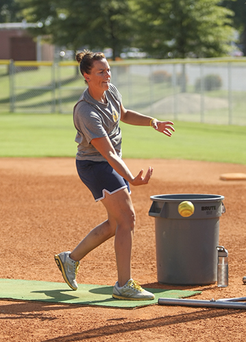 Haley Hays/The News Head Coach Kara Amundson pitches to her team at practice earlier this season.