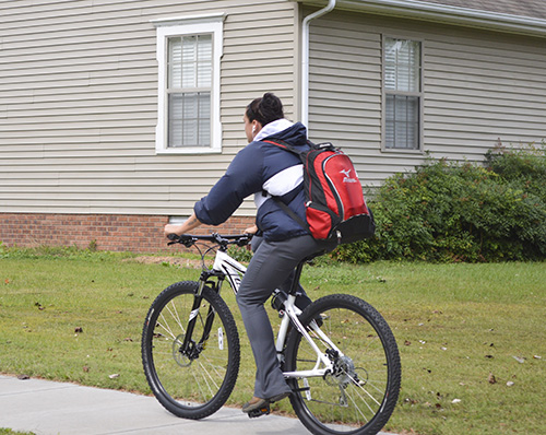 Hannah Fowl/The News A commuter student bikes on a city sidewalk after class since bike lanes do not exist on the road.