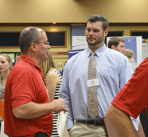 Hannah Fowl/The News Drew Kelley (right), senior from Thompson's Station, Tenn., speaks with a potential employer at the Career Fair.