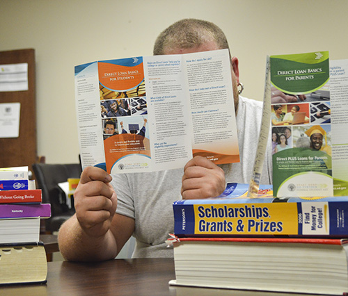 Photo Illustration by Hannah Fowl/The News A student reads brochures on how to take out loans, the different loans available, receiving scholarships and grants and how to pay for college.