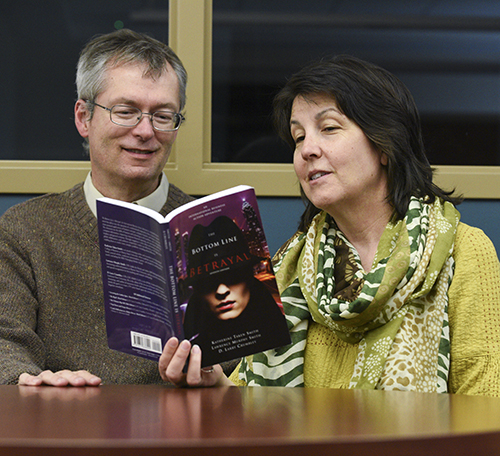 "Kory Savage/The News Professors Lawrence Murphy and Katherine Smith look at their novel, ""The Bottom Line is Betrayal."""