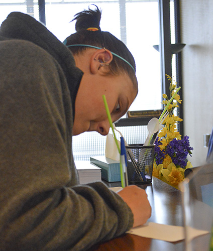 Hannah Fowl/The News Maci Dungan, sophomore from Miamisburg, Ohio, fills out forms for financial aid.