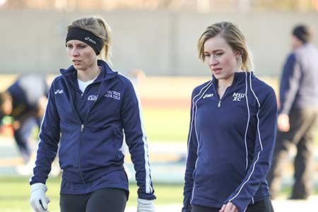 Haley Hays/The News Junior Emma Gilmore (right) breaks the school record by running a 4:59.58 mile.