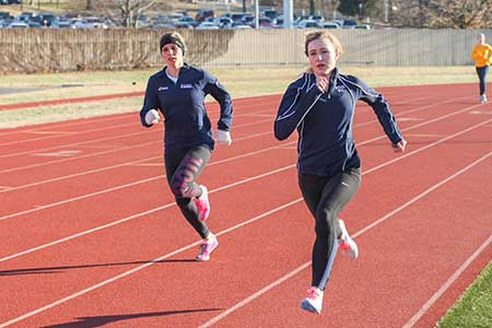Haley Hays/The News Junior distance runner Emma Gilmore and senior mid-distance runner Brittany Bohn run around the track during practice.