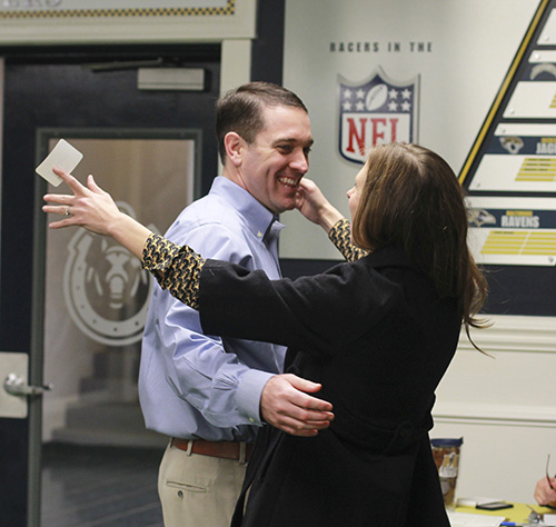 Jenny Rohl/The News Head Coach Mitch Stewart embraces his wife at a signing day meet-and-greet Feb. 4 at the Racer Room in Roy Stewart Stadium.