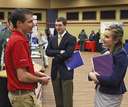 Nicole Ely/The News Tori Heddinger, junior from Mariah Hill, Ind., and Austin Reed, junior from Monticello, Ill., speak with agricultural company representatives.