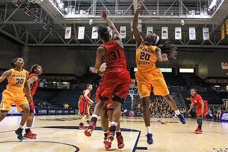 Kalli Bubb/The News Freshman forward and guard, Ke'Shunan James jumps for the block against Cougars freshman guard, Donshel Beck.