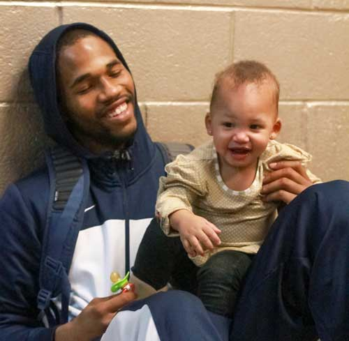 Jenny Rohl/The News Senior guard T.J. Sapp plays with his daughter outside the locker room after the Racers' OVC Championship loss March 7.